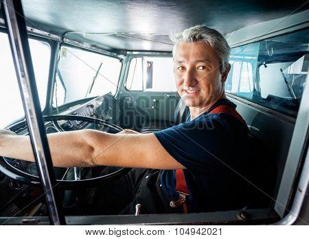 Portrait of confident mature fireman driving firetruck at station
