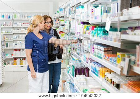 Female pharmacist removing product for customer from shelf in pharmacy