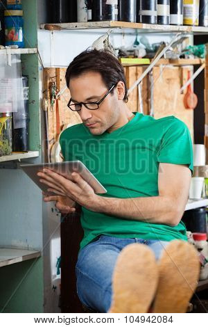 Relaxed worker using digital tablet while sitting in paper factory