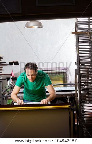 Mid adult worker using squeegee in paper factory
