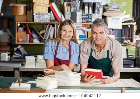 Portrait of happy male and female workers with notebook and papers in factory
