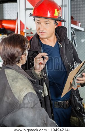 Confident male firefighter discussing with female colleague at fire station
