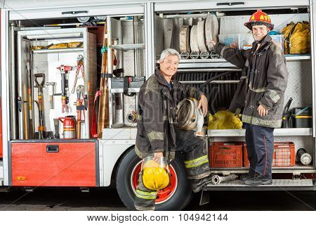 Portrait of confident male firefighters standing on truck at fire station