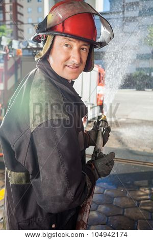 Side view portrait of smiling mature fireman spraying water during practice at fire station