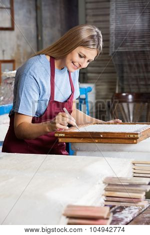 Smiling mid adult female worker cleaning paper using tweezers in factory