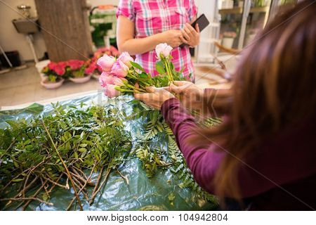 Cropped image of florist making bouquet of roses for female customer in flower shop