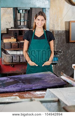 Portrait of smiling female worker with hands in pockets standing in paper factory