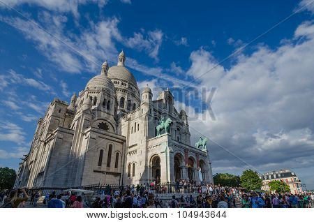 Sacre-Coeur Basilica towers over the people visiting the popular tourist site