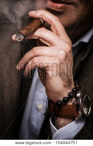 elegant man wearing suit and white shirt smoking  cigar indoor shot, closeup, selective focus