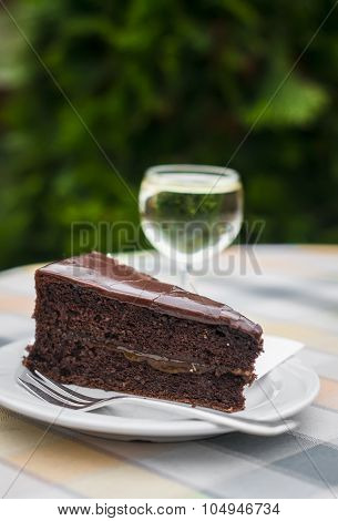 Piece Of Chocolate Cake On A White Plate And A Glass Of White Wine In An Italian Café
