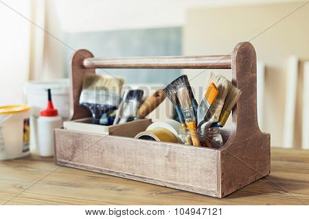 Paint brushes and supplies in wooden toolbox