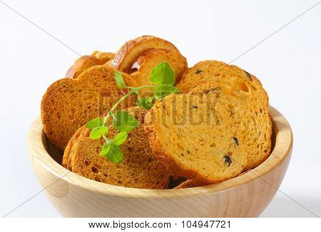 close up of bread rusks with black olives in wooden bowl
