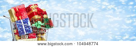 Shopping cart with Xmas gifts over snowy banner background.