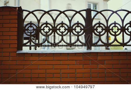 Black wrought iron and brick fence