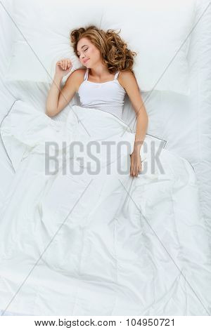 Shot of a young woman sleeping on a bed .