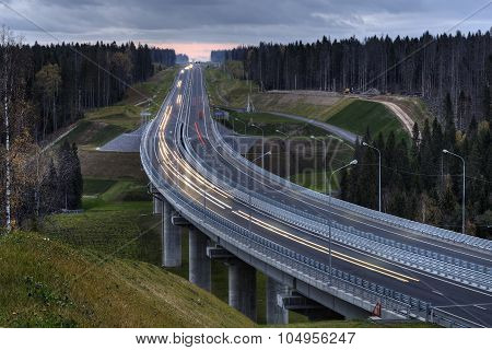 A Highway Crosses The Russian Forest At Night.