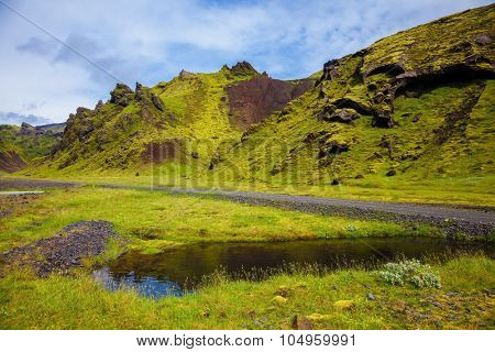Picturesque basalt hills overgrown green grass and polar moss. On bottom of canyon many streams flow. Canyon Pakgil in Iceland