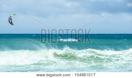 Big sea waves and kite-surfer enjoying extreme water sport