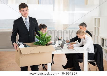 Businessman Carrying Belongings While Other People Working