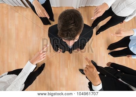 Businesspeople Pointing At Businessman