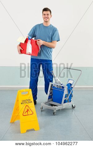 Worker With Cleaning Equipments And Wet Floor Caution Sign
