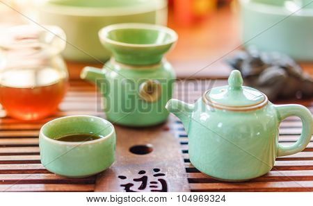 Green Teapot And Teacup With Tea Bag On A White Textured Photo. Natural Colors