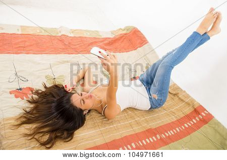 Pretty brunette wearing denim jeans and white top lying down on bedsheets, hair spread out, holding