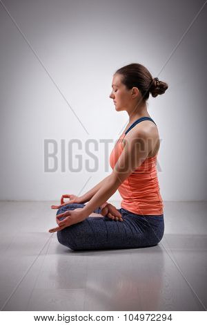 Beautiful fit yogini woman meditating  in yoga asana Padmasana (Lotus pose) cross legged position for meditation with Chin Mudra - psychic gesture of consciousness