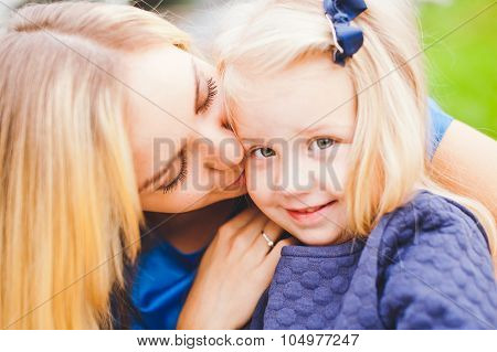 Young Mom And Her Cute Little Daughter In Blue Dresses Relaxing In Park In Summer