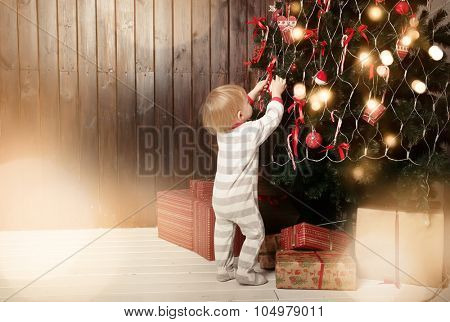 Back view of toddler boy decorating Christmas tree