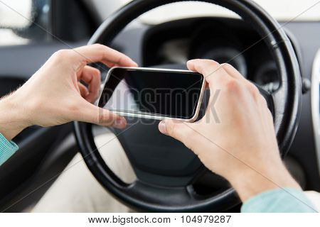transport, business trip, technology and people concept - close up of young man hand with smartphone driving car