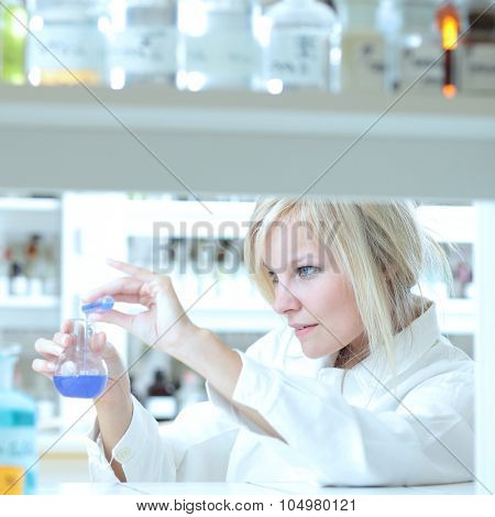 Closeup of a female researcher carrying out an experiment in a lab