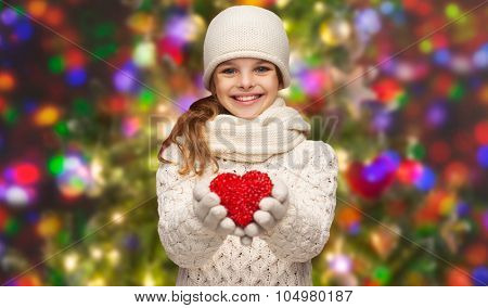 christmas, winter, holidays and childhood concept - smiling teenage girl in winter clothes with small red heart over glitter or lights background