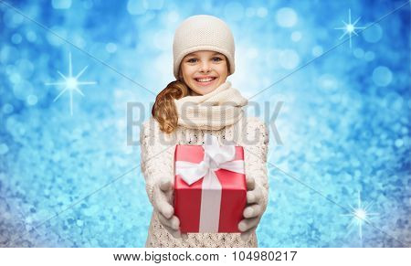 christmas, winter, holidays and childhood concept - smiling girl in hat, muffler and gloves with gift box over blue glitter or lights background