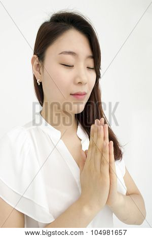Peaceful asian woman meditating with hands together