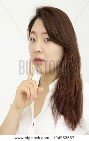 Beautiful asian woman with finger on lips