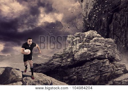 Rugby player running with the ball against rock crashing down from cliff