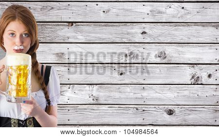 Oktoberfest girl drinking jug of beer against digitally generated grey wooden planks