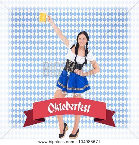Pretty oktoberfest girl holding beer tankard against blue pattern