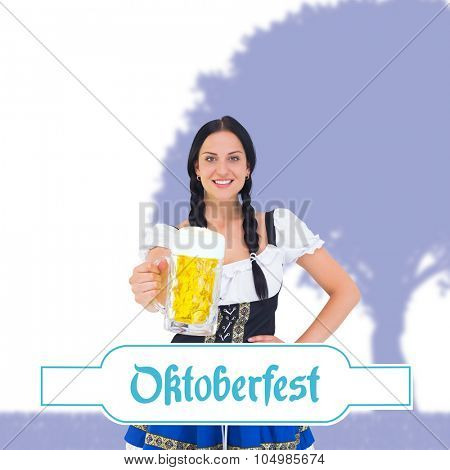Pretty oktoberfest girl holding beer tankard against oktoberfest banner
