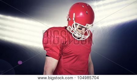 Unsmiling american football player looking down against spotlights