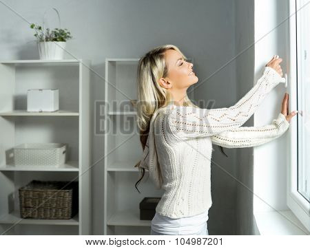 Young and beautiful blond woman touching the radiator. Heating season concept.