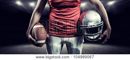 Mid section of sportsman holding American football and helmet against rugby stadium