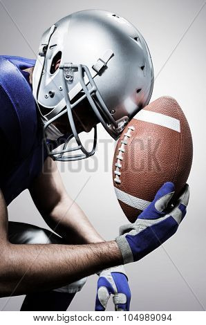 Close-up of upset American football player with ball against grey background