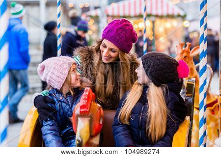 Family riding the carousel on Christmas market