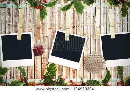 Christmas photos on a line against wooden background in pale wood