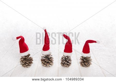 Four fir cone with red santa hats on snowy white wooden background for christmas decoration.