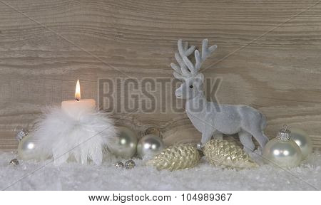 One burning advent candle with deer on wooden brown shabby background.
