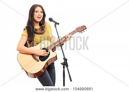 Female musician playing a guitar and singing on a microphone isolated on white background