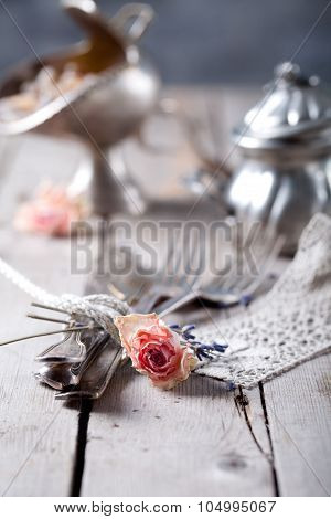 Old vintage cutlery bound with a rope, dried rose